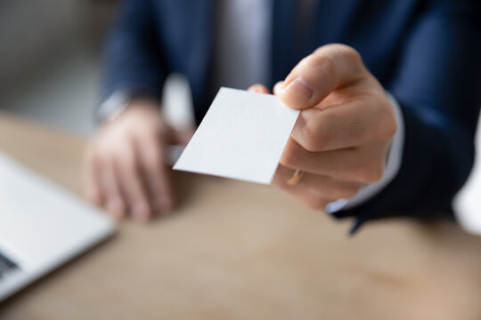 Crop close up of businessman stretch hand with empty white mockup business card offer contact to client or partner. Male employee suggest personal information to customer. Acquaintance concept.