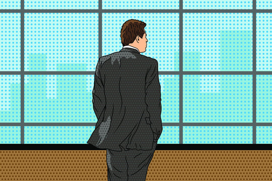 A young man in a businessman suit stands near the window and looks at the city.