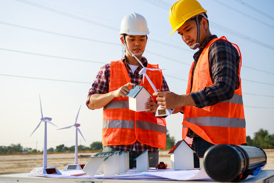 Asian engineer, foreman or leader discussion about home solar cell and wind turbine model in construction site project and High voltage power line pylon in the background. Teamwork, Leadership concept