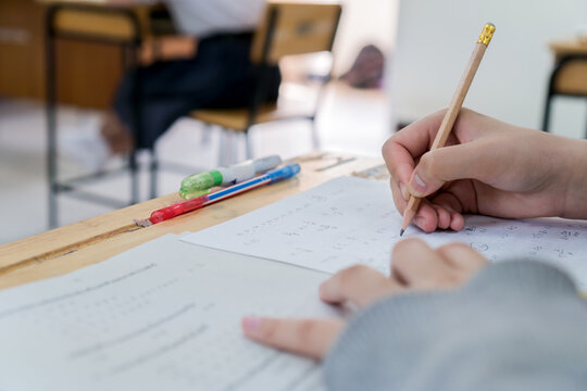 student taking notes lecture in high school or university with holding pencil writing on paperwork sheet and taking final exam in examination classroom