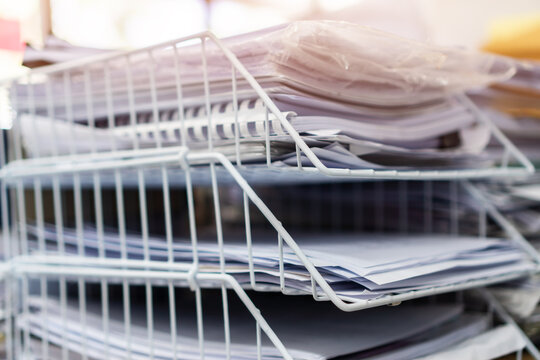 Stack of paper documents information of finance files tray on commercial report papers or piles of unorganized achieves, paperwork on teacher at university, sheet book assessment legal at workplace