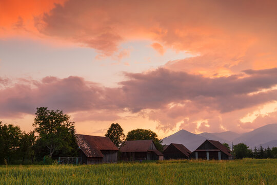 Clearing storm over a rural landscape with a traditional barn.