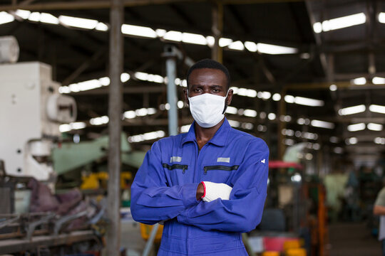 Portrait of black male engineer wearing protective medical face mask at work in the industry factory. African American male worker wearing protective medical face mask for health in the factory