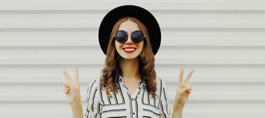 Fototapeta Portrait of stylish smiling young woman wearing a striped shirt and black round hat on a white background