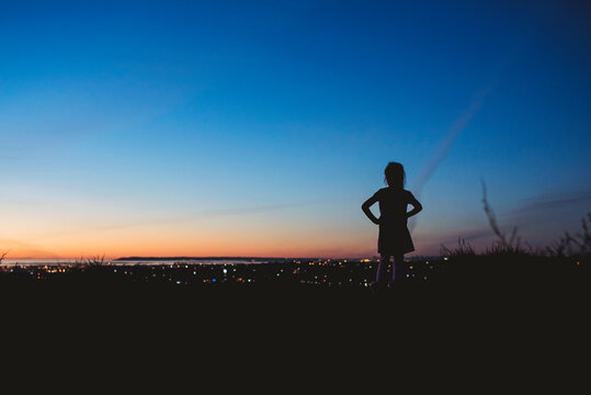Silhouette of young girl with hands on hips looking at San Diego
