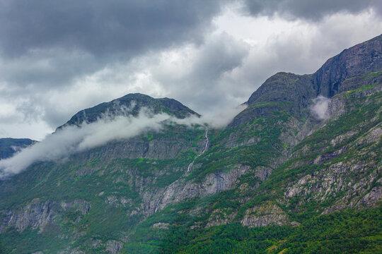 Fog mist clouds waterfalls on mountain norwegian landscape Jotunheimen Norway.