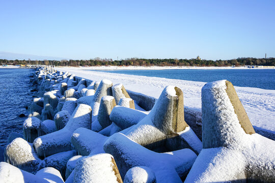 winter seascape, port entrance with snow covered concrete breakwater