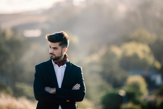 Portrait of young man in suit outdoor by field at sunset
