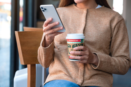 Jan 26th 2021 : A woman holding and using Iphone 11 Pro Max smart phone while drinking coffee at Starbucks coffee shop, Chiang mai Thailand
