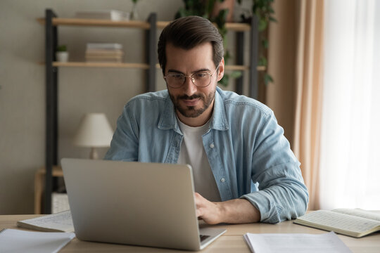 Attentive millennial male manager employee busy at telework at quarantine time study documents in corporate network from home pc. Concentrated young man specialist doing remote computer work on laptop