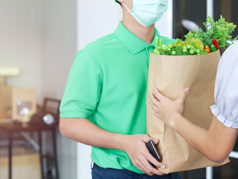 Young Asian delivery man in green T-shirt uniform and cap wearing face mask to prevent covid19 infection, carrying package bag of grocery food; vegetables and fruit, from store and giving goods to cus
