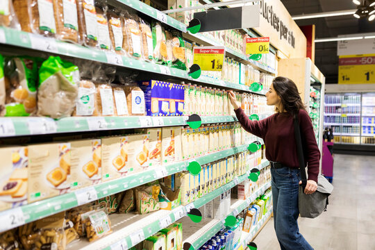Woman choosing products from supermarket dairy shelf area