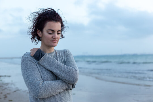 Portrait of an introspective woman hugging herself on the beach