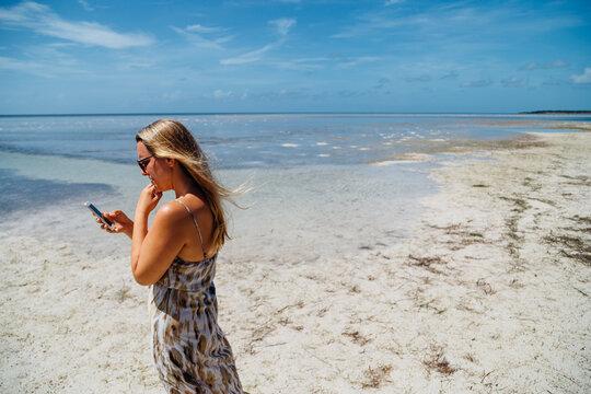 Woman checks her phone on beach
