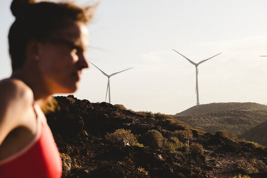 Blurred silhouette of female runner standing against wind mills