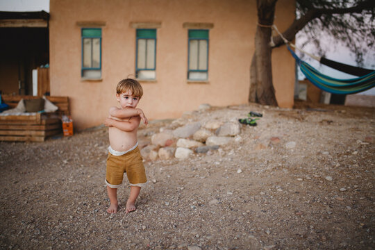 A young boy standing in the desert looking forward