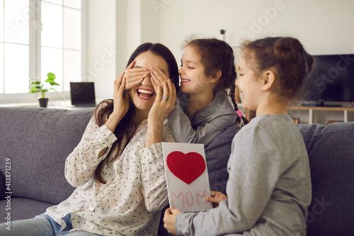 Surprise for mom. Two cute twin sisters close their mother's eyes when they give her a handmade card. Sisters are going to congratulate mom on the holiday. Concept of women's day or mother's day.