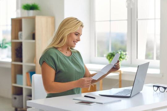 Happy young woman sitting at desk at home reading monthly statement or document notifying about business loan approval, college or university admission, winning scholarship, or getting money refund