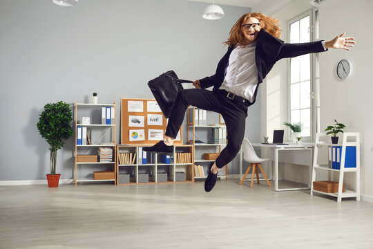 Overjoyed employee leaving office at the end of day. Young man having fun as it's time to finish work. Funny white-collar worker is so happy that workday is over that is jumping high ready to fly home