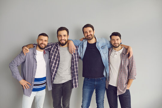 Group of cheerful friends having fun together. Portrait of happy bearded young men standing with arms around each other's shoulders and smiling at camera in studio with light gray background