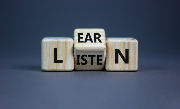 Listen and learn symbol. Turned a wooden cube and changed the word 'listen' to 'learn'. Beautiful grey background, copy space. Business, education and listen and learn concept.