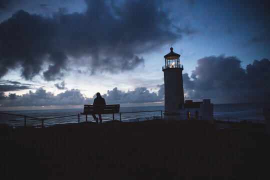 Silhouette man sitting on bench at beach against cloudy sky during sunset
