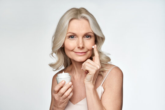 Smiling 50s middle aged mature woman putting tightening facial cream on face looking at camera. Anti age healthy dry skin care beauty therapy concept, skincare rejuvenation treatment against wrinkles.