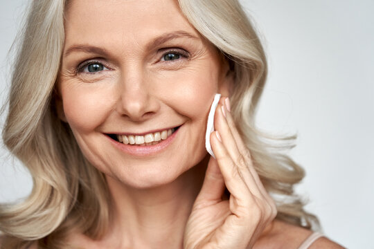 Smiling 50s middle aged older woman holding cotton pad sponge cleansing face skin with cleanser, happy mature lady removing makeup enjoy healthy clean anti age dry skincare beauty treatment.