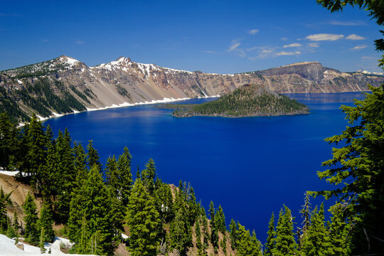 Wizard island at Crater Lake National Park. You can see the brilliant blue water. There is a blue sky with a few clouds and green trees.