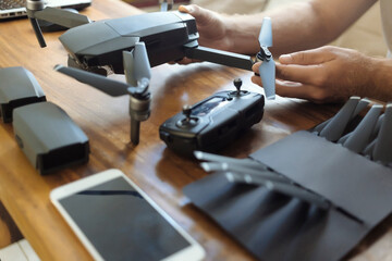 Cropped hands of engineer examining quadcopter on table at office Wall mural