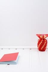 Obraz Biały blat drewniany ananas czerwony origami i notes czerwony - fototapety do salonu
