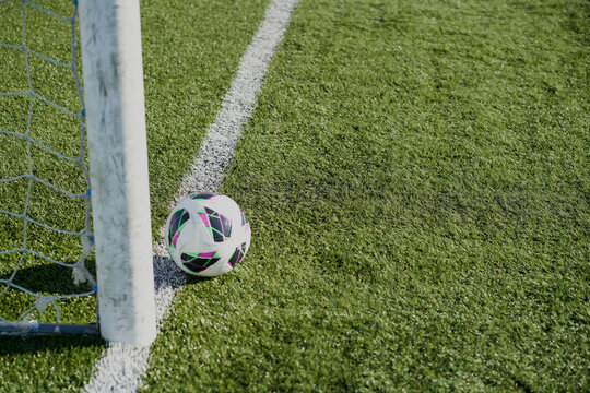 Football soccer goals and ball on clean empty green field