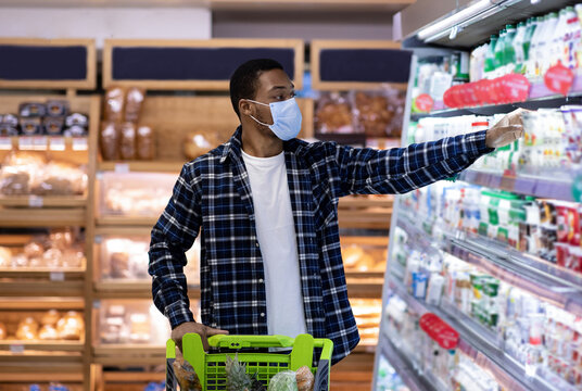 Young black man in protective mask buying dairy products at supermarket during coronavirus quarantine