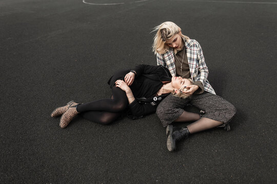 Two girlfriends in fashionable casual clothes on basketball court. Trendy girl in vintage black clothes lies on friend's lap in checkered blazer. Modern fashion models in beautiful everyday wear.
