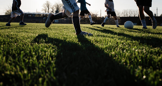 Low section of man playing soccer with children on grassy field at park during sunset