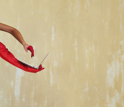 hands in red gloves hold a laptop on a yellow-beige textured wall background side view
