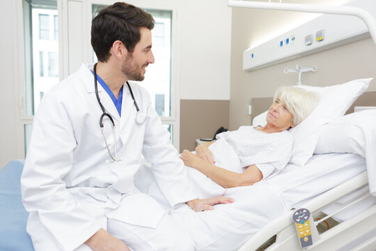 male doctor checking senior woman at home
