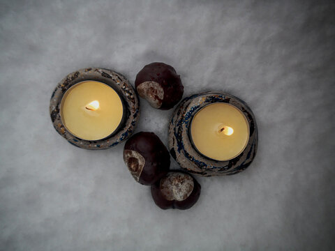 chestnut and candles with flame on snow in cold winter