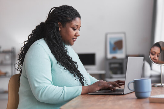 Side view portrait of curvy African American woman using laptop at desk and typing while enjoying work from home in minimal interior, copy space