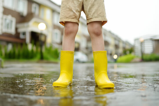 Little boy wearing yellow rubber boots walking on rainy summer day in small town. Child having fun. Games for children in rain.