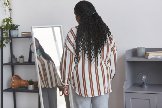 Minimal back view portrait of overweight African American woman looking in mirror while trying on clothes at home, copy space