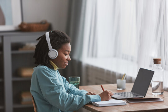 Side view portrait of young African American woman studying or working at home and smiling while wearing headphones, copy space