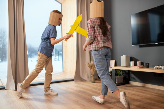 Playful siblings in casualwear and cardboard helmets fighting with toy swords