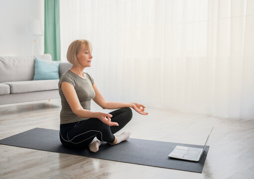 Peaceful senior woman meditating with closed eyes in front of laptop computer at home, copy space