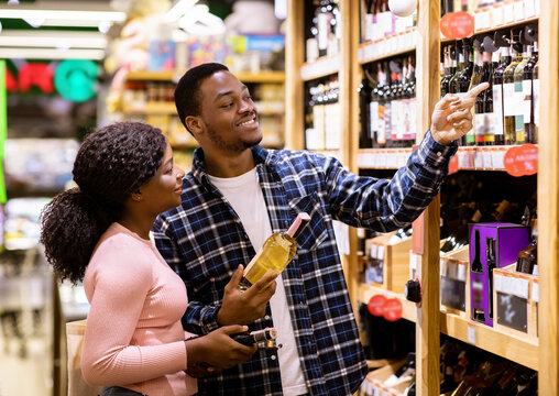 Happy black man and his girlfriend buying wine at liquor department of supermarket