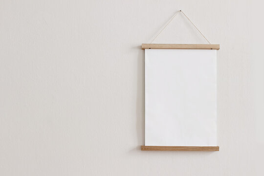 Blank wooden picture frame hanging on beige wall. Empty poster mockup for art display. Minimal interior design.Front view, copy space. No people.
