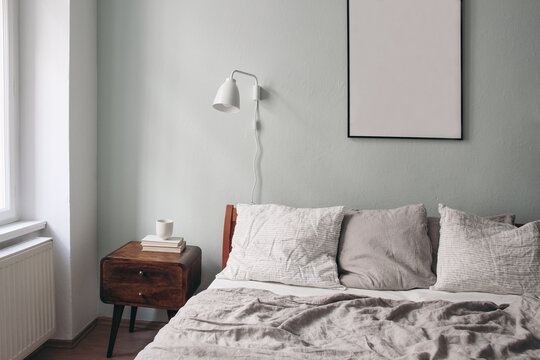 Bedroom view. Grey linen and white linen pillows on wooden bed. Scandinavian interior. Cup of coffee and books on retro wooden bedside table. Portrait black picture frame mockup on sage green wall.