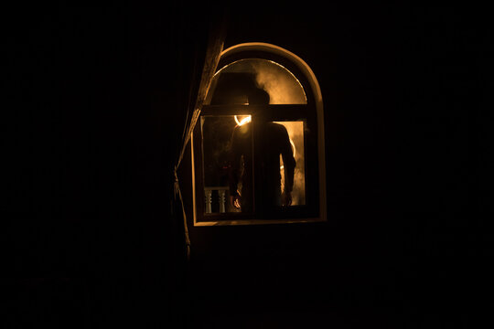 Silhouette of an unknown shadow figure on a door through a closed glass door. The silhouette of a human in front of a window at night.