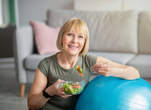 Exercise and healthy diet concept. Senior woman with fitball eating fresh vegetable salad at home