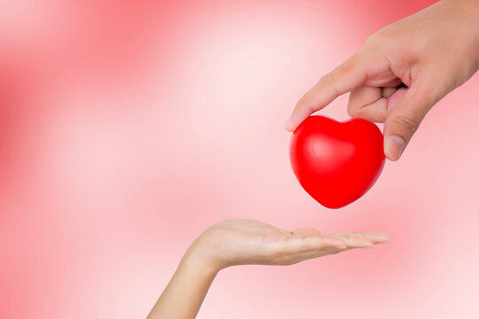 Hand of man giving red heart shape to woman, valentine day and love, relationship and romance, charity and volunteer, donate and donor, emotion and faith, help care, support and affectionate.